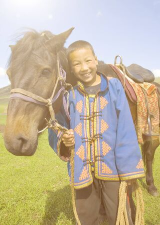 tilting: Little boy tilting his head to his horse and smiling at outdoors.