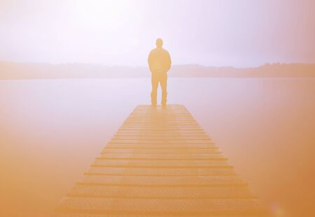 deliberation: Man standing on a jetty by tranquil lake. Stock Photo