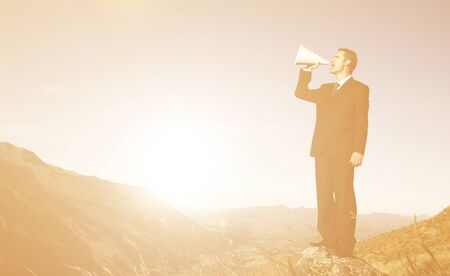 stating: Businessman shouting on the top of the mountain. Stock Photo