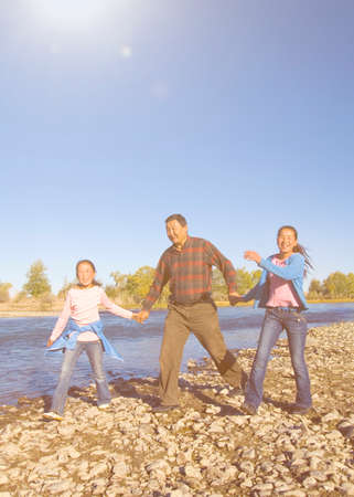 farther: Mongolian Family Anjoy Walking by The River Concept Stock Photo