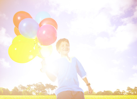 dozen: Happy Boy Outdoors With A Dozen Of Helium Balloons Concept