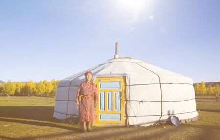 independent mongolia: Mongolian lady standing in front of the tent in scenic view.