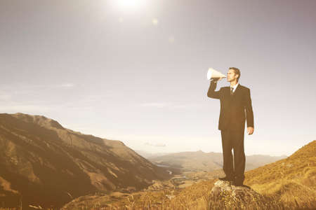 businessman using a megaphone: Businessman shouting on the top of the mountain. Stock Photo