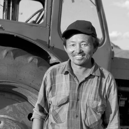 mongolian: Smiling Mongolian Farmer Standing Tractor Concept Stock Photo