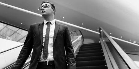 go inside: Business Man Walking Down Escalator Concept