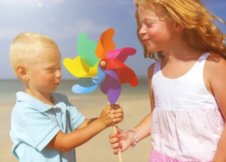 multi age: Brother and sister blowing on windmill at the beach.