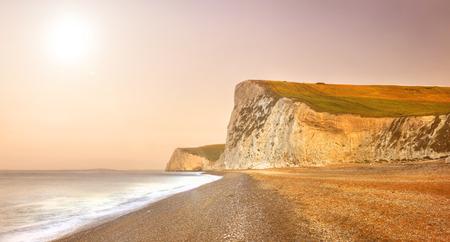 durdle door: Durdle Door dramatic Jurrasic coastline at sunrise. Dorset, the UK. Stock Photo
