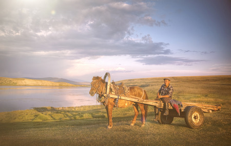 horse cart: Horse Man Sitting On A Horse Cart In A Scenic View Of Nature Concept