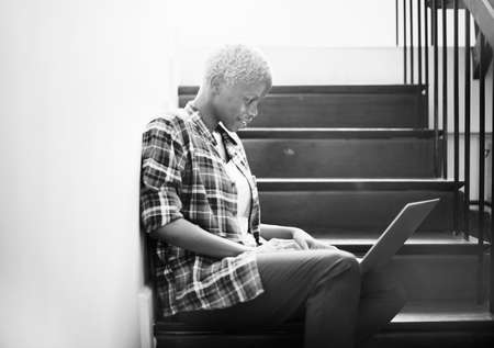 woman searching: African Woman Searching Internet Sitting on Steps