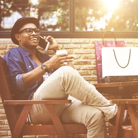 african culture: Man Shopping Outdoor Talking Mobile Phone Concept