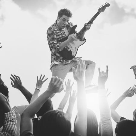 concerto rock: Hombre joven con una guitarra Realizar en un muchedumbres extáticas