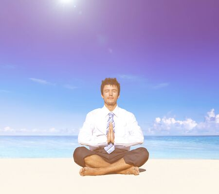 away from it all: Businessman meditating on the beach. Stock Photo