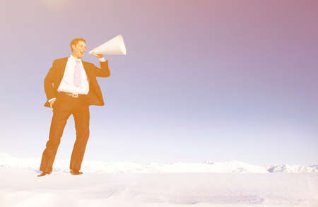 stating: Businessman shouting on snow covered mountain.
