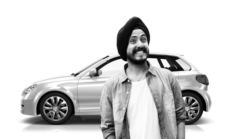 Man with turban smiling with a car in the background