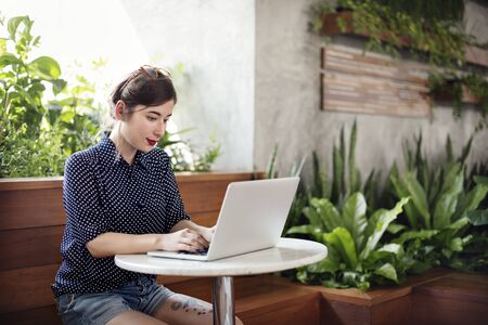comtemporary: Woman Using Laptop Working Browsing Concept