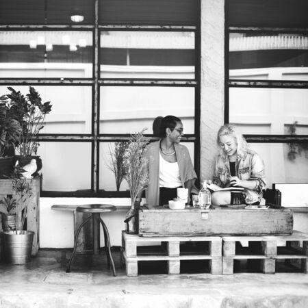 tomando café: Amigos que hablan de chicas sonrientes al aire libre Concepto Foto de archivo