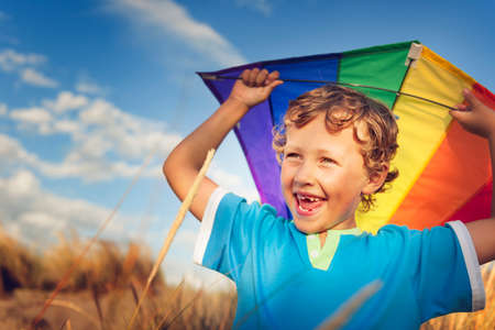flying kites: Little Boy Playing Kite Fun Happiness Enjoyment Outdoors Concept Stock Photo