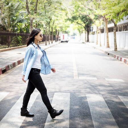 paso peatonal: Mujer que camina por la ciudad del paso de peatones Concepto estilo de vida