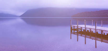 deliberation: Tranquil peaceful lake with jetty , New Zealand. Stock Photo