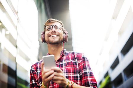 escuchando musica: Hombre que recorre Escuchar Misic auriculares Concepto informal Foto de archivo