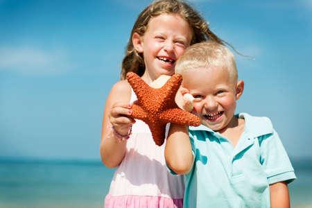 adolescence: Playa de las estrellas de mar Niño rubio lindo concepto del mar Adolescencia Foto de archivo