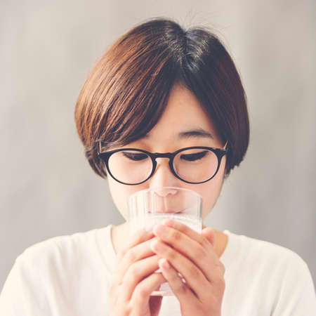 grow up: Asian Girl Drinking Milk Beverage Grow Up Relaxation Concept Stock Photo