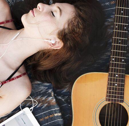 lie down: Girl Guitar Earphones Digital Device Lie Down Concept