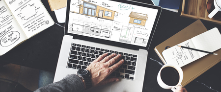Man using a laptop with floor plan Stock Photo