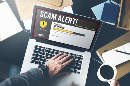 Man using a laptop with scam alert concept