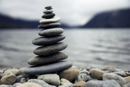 deliberation: Zen balancing pebbles next to a misty lake. Stock Photo