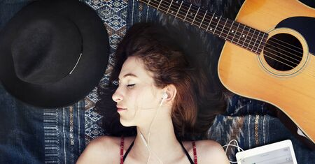 down beat: Girl Guitar Earphones Digital Device Lie Down Concept