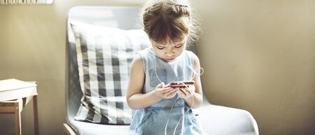 digital device: Small Girl Browsing Mobile Phone Concept