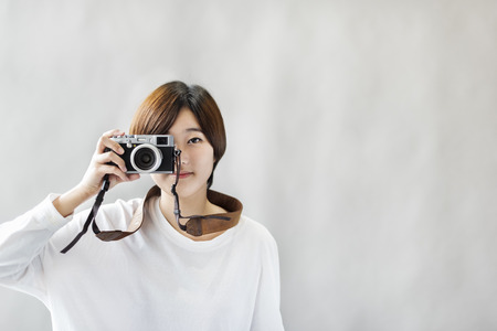 アジアの女の子のカメラ写真フォーカス撮影のコンセプト