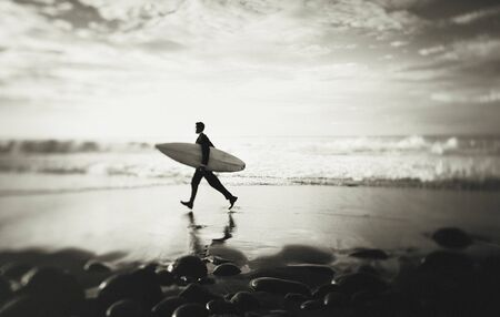 getting away from it all: Lone Businessman by the Beach with Surfboard Concept