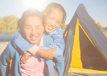 campsite: Happy Mongolian girls playing piggyback at campsite. Stock Photo
