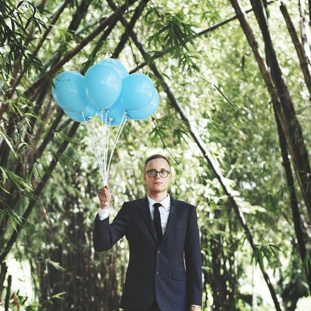 releasing: Businessman Holding Balloons Nature Concept Stock Photo