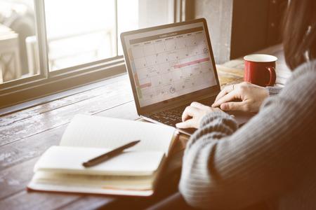 Asiatische Dame Typing Laptop Kalender Cafe Konzept Standard-Bild