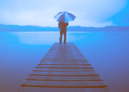 deliberation: Man Holding an Umbrella on a Jetty by Tranquil Lake Concept