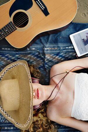 down beat: Girl Guitar Beach Music Song Headphone Rhythm Concept Stock Photo