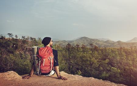 男一人で崖バックパッカー概念を座っています。