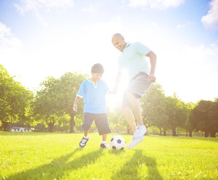 preadolescent: Little boy playing soccer with his father. Stock Photo