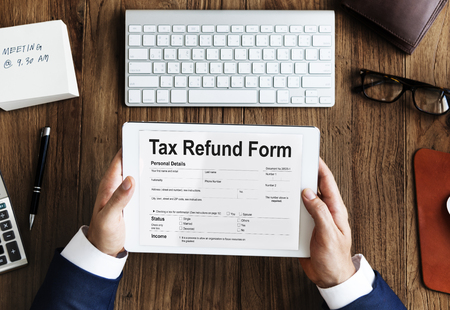 Businessman holding a digital tablet with tax refund form Stock Photo