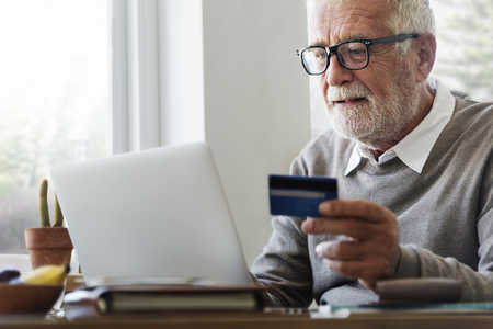 holding credit card: Senior Adult Holding Credit Card Concept Stock Photo