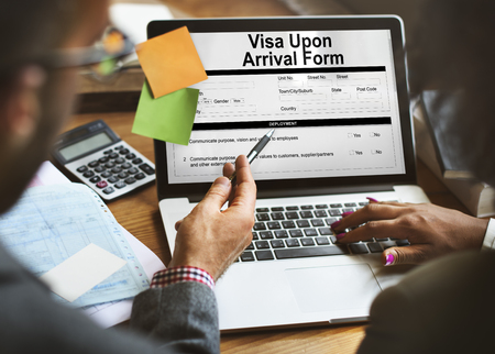 Man and woman checking a visa upon arrival form in a laptop Stock Photo
