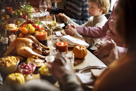 感謝祭のお祝い概念を祈って手を繋いでいる人々 写真素材