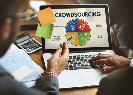 People using a laptop with crowdsourcing concept Stock Photo
