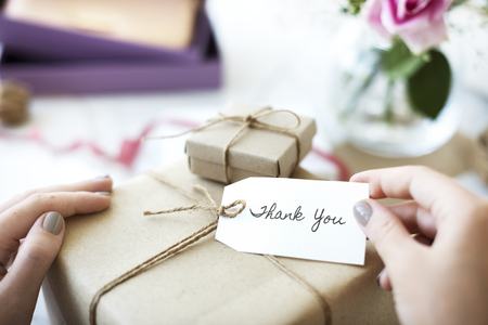 Woman holding a present with thank you label