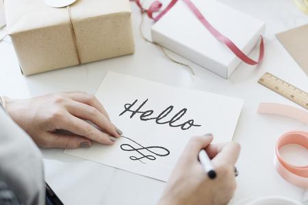 Woman writing hello on a paper Reklamní fotografie