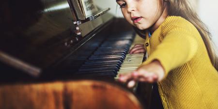 Adorable Cute Girl Playing Piano Concept Stock Photo