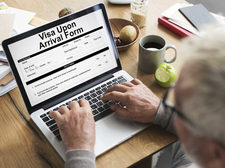 Man using a laptop with visa upon arrival form